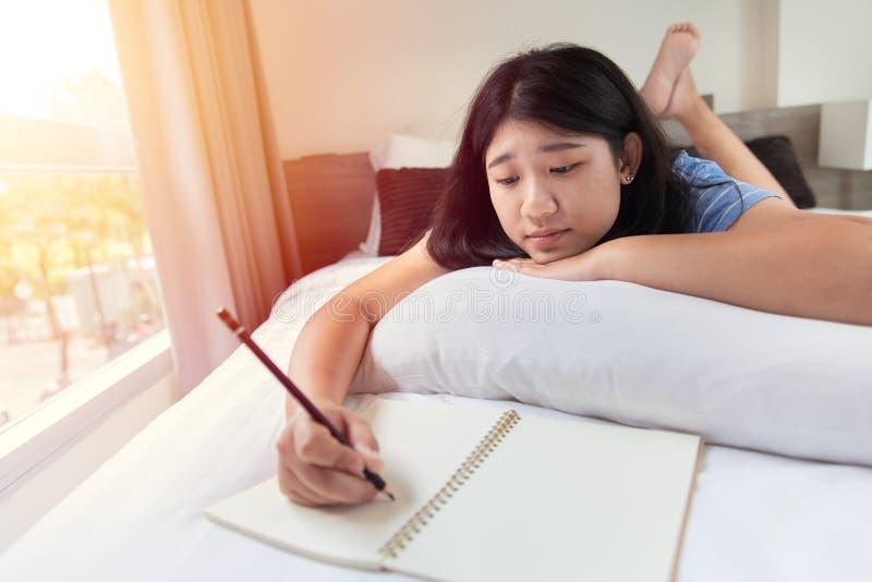 A menina adolescente relaxa fazendo trabalhos de casa em casa na cama no quarto imagem de stock