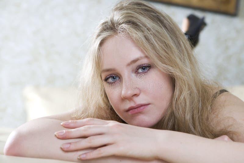 Menina adolescente só loura que encontra-se na cama imagem de stock royalty free
