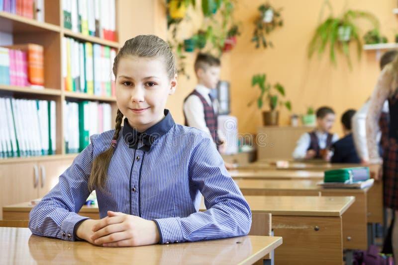 Menina adolescente sentada na mesa na sala de aula, crianças em segundo plano fotografia de stock
