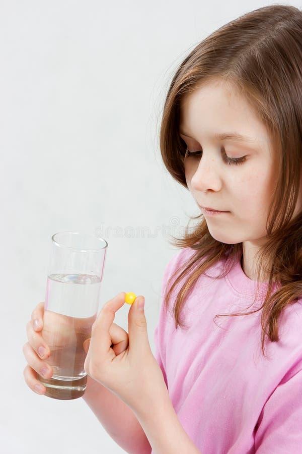 A menina adolescente toma a medicina fotos de stock