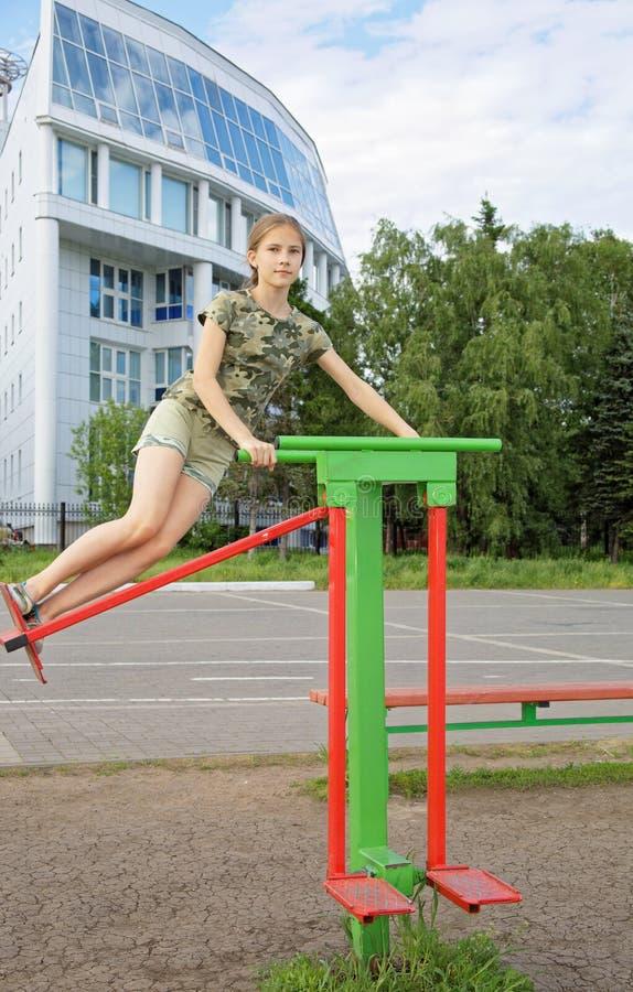 A menina adolescente treina em um simulador de balanço fora imagens de stock royalty free