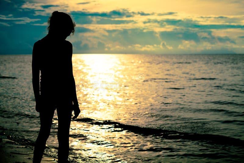 Menina adolescente triste que está na praia fotografia de stock
