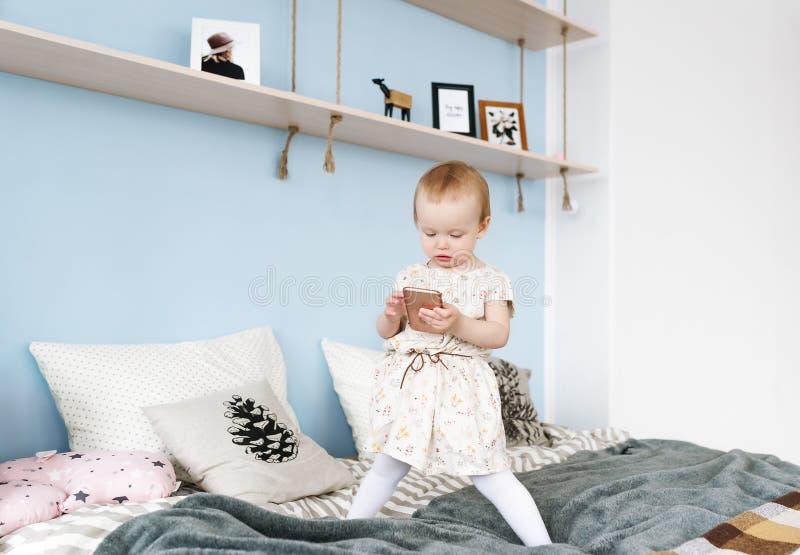 A menina adorável acordou acima em sua cama, jogando no telefone imagem de stock royalty free