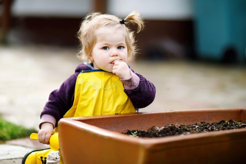 Menina adorável bonito da criança que joga com areia e pá no dia de mola A criança do bebê que vestem botas amarelas e a lama cho fotos de stock
