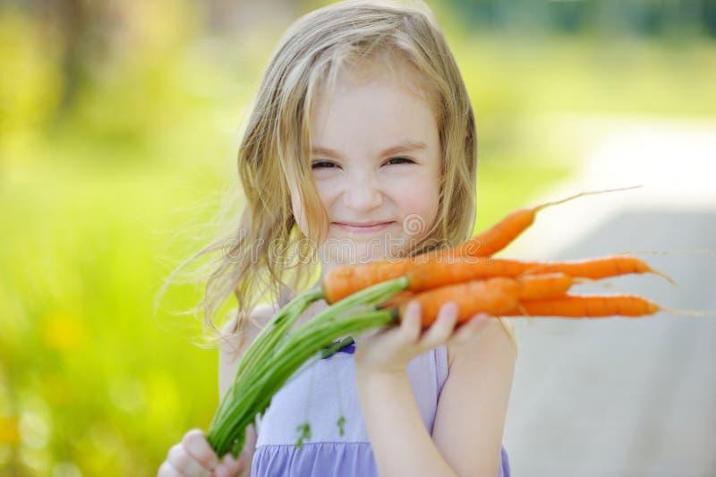 Menina adorável com cenouras fotos de stock royalty free