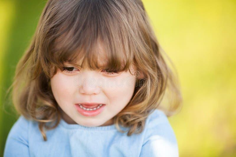 Menina adorável com a expressão triste de sua cara, indo gritar fotografia de stock royalty free