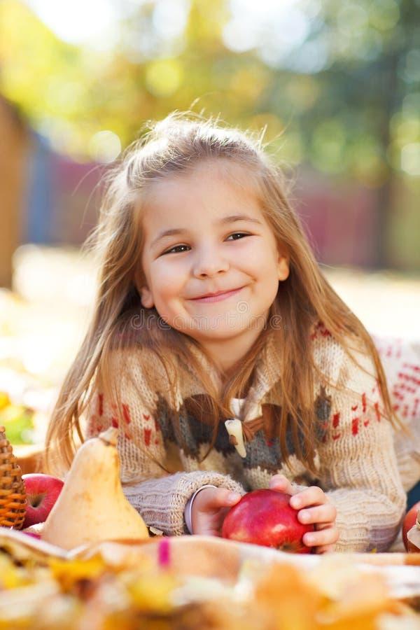 Menina adorável com folhas e maçã de outono foto de stock royalty free