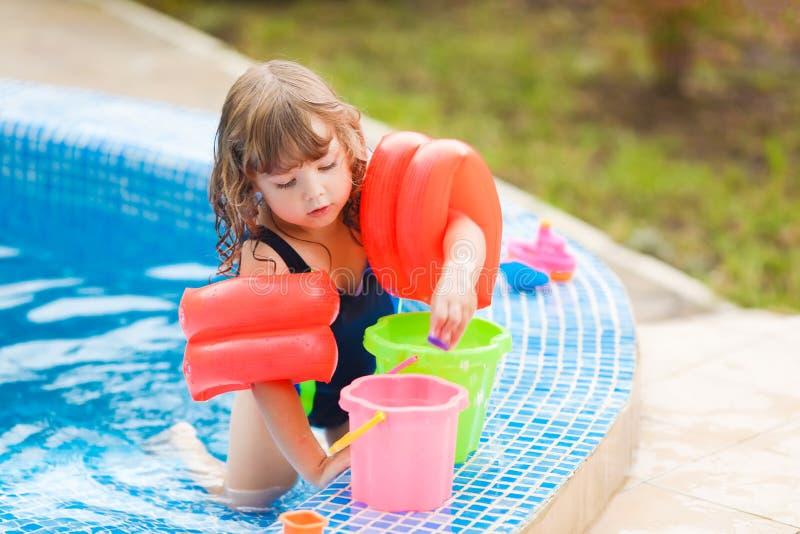 Menina adorável com os flutuadores infláveis das sobre-luvas que sentam-se na piscina imagens de stock