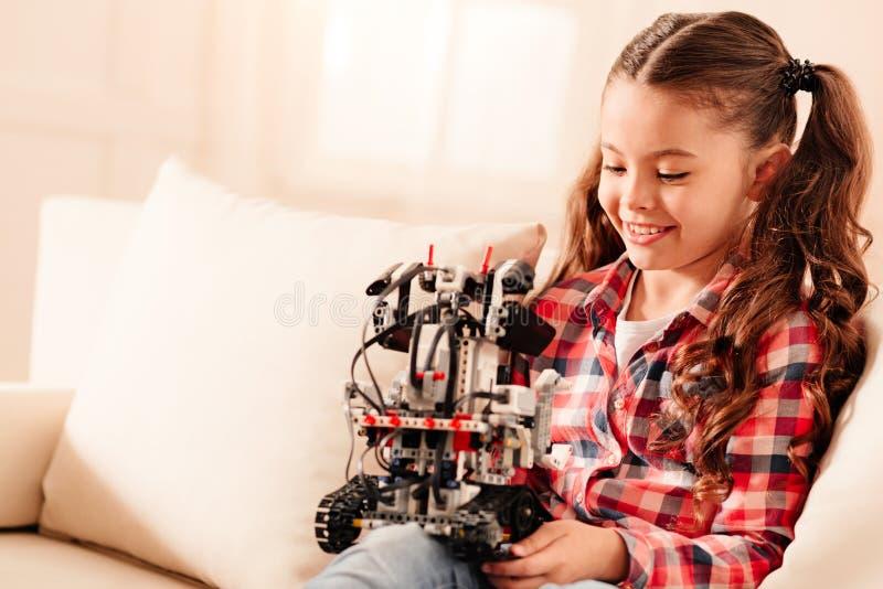 Menina adorável com rabos de cavalo que examina o robô em casa imagem de stock royalty free