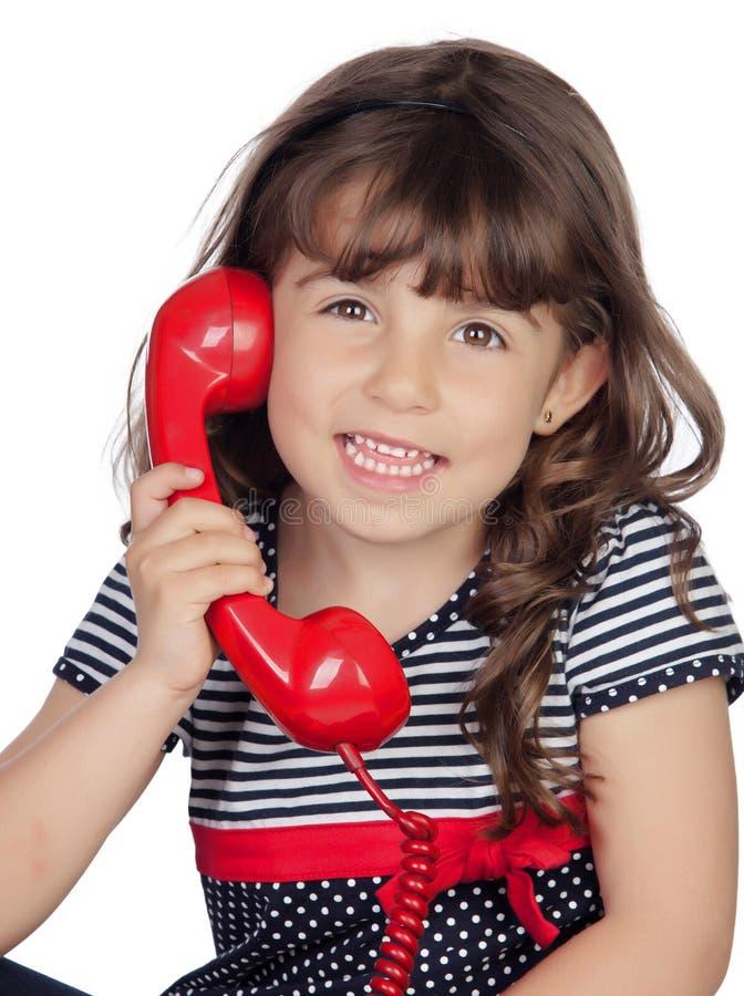 Menina adorável com telefone vermelho fotografia de stock