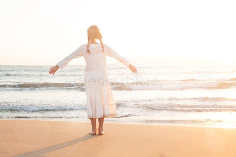 A menina adorável da criança olha o céu e o mar fotografia de stock