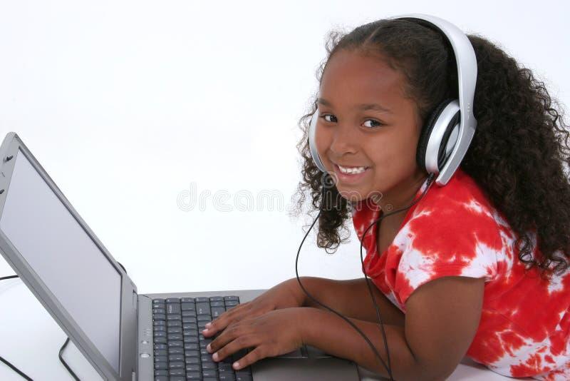 Menina adorável dos anos de idade seis que senta-se no assoalho com computador portátil foto de stock royalty free