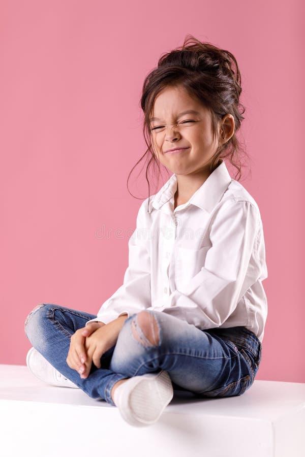 Menina adorável na camisa branca com penteado no fundo cor-de-rosa Emoções humanas e expressão facial imagem de stock