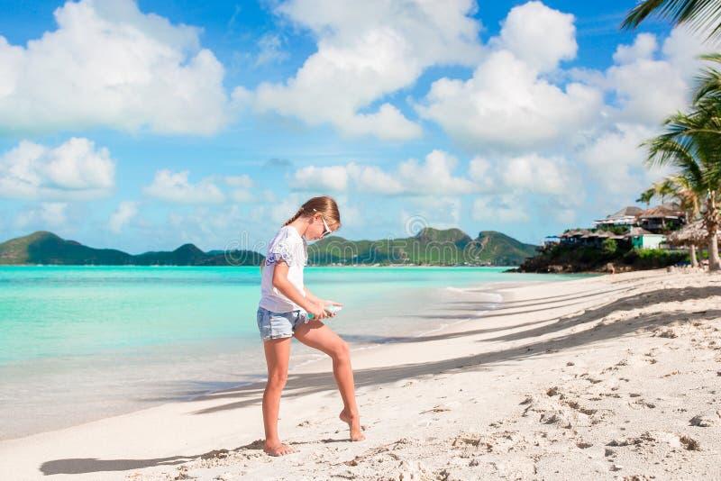 Menina adorável na praia tropical que aplica o creme do sunblock imagem de stock royalty free