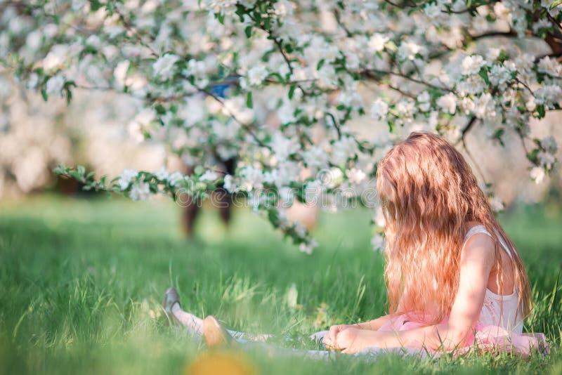 Menina adorável no jardim de florescência da árvore de cereja no dia de mola foto de stock royalty free