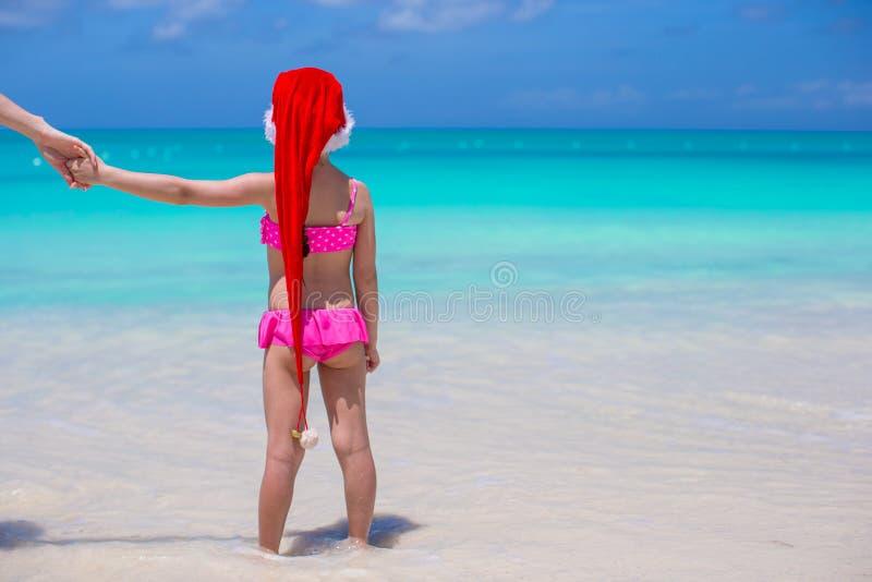 A menina adorável pequena em Santa Hat vermelha aprecia a praia fotos de stock