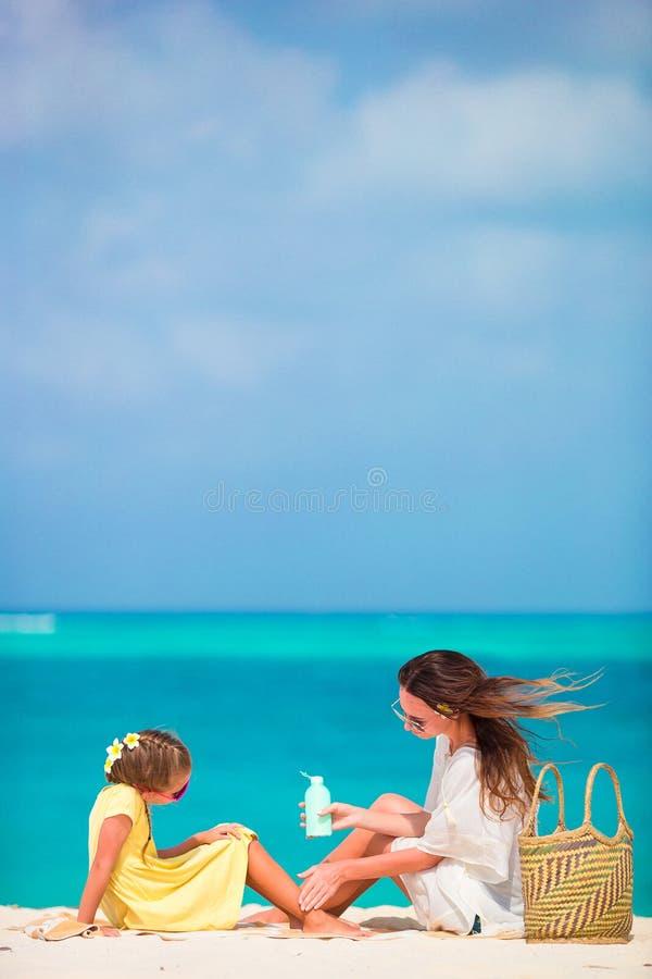 Menina adorável pequena que aplica o creme do sol a seu nariz da mãe fotografia de stock royalty free