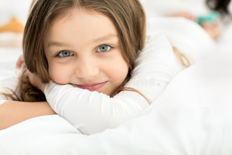 Menina adorável pequena que encontra-se e que relaxa na cama em casa imagens de stock royalty free