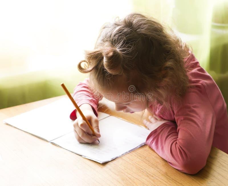 Menina adorável pequena que escreve lhe trabalhos de casa no livro de exercício imagens de stock