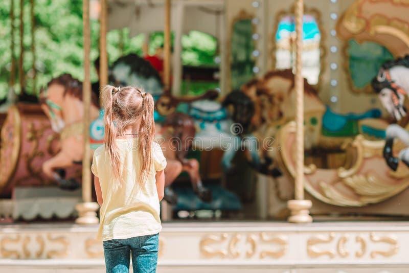 Menina adorável perto do carrossel fora imagem de stock royalty free
