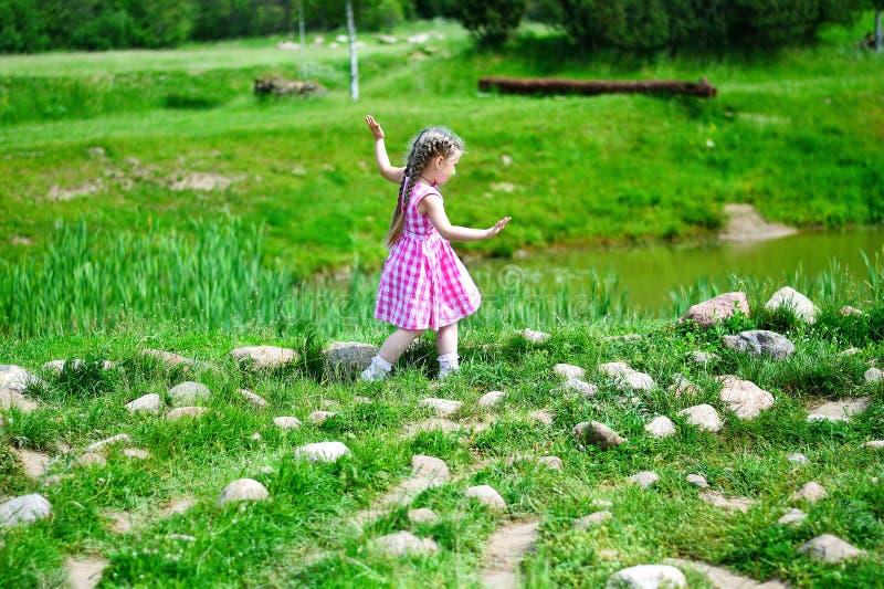 Menina adorável que anda nas rochas por uma lagoa na paridade ensolarada imagens de stock