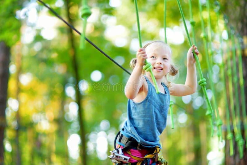 Menina adorável que aprecia seu tempo no parque de escalada da aventura no dia de verão morno e ensolarado fotografia de stock