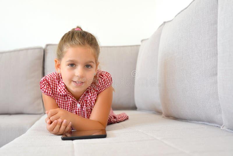 Menina adorável que aprende com seu dispositivo da tabuleta fotos de stock royalty free