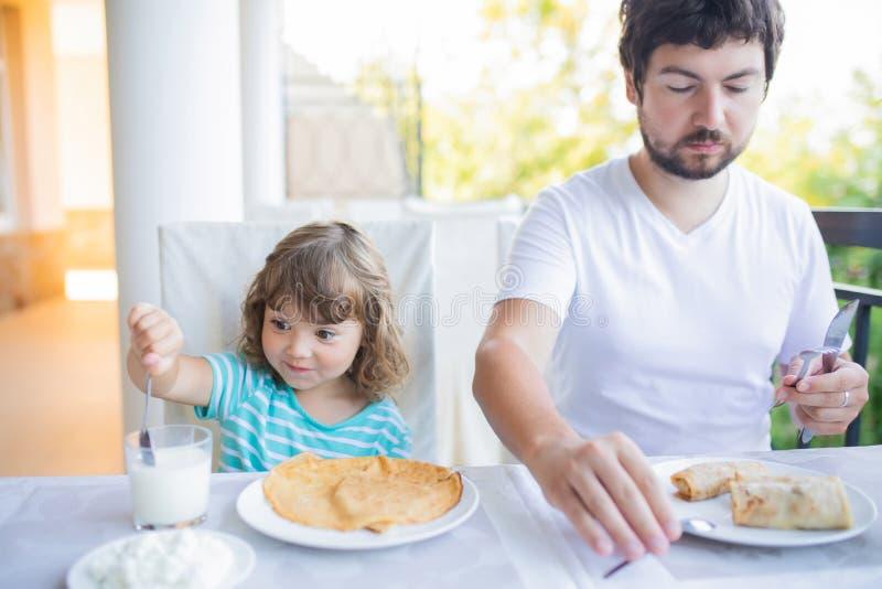 Menina adorável que come o café da manhã com seu pai, comendo panquecas e o leite bebendo fotografia de stock