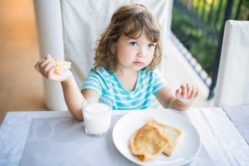 Menina adorável que come o café da manhã, comendo panquecas e o leite bebendo foto de stock