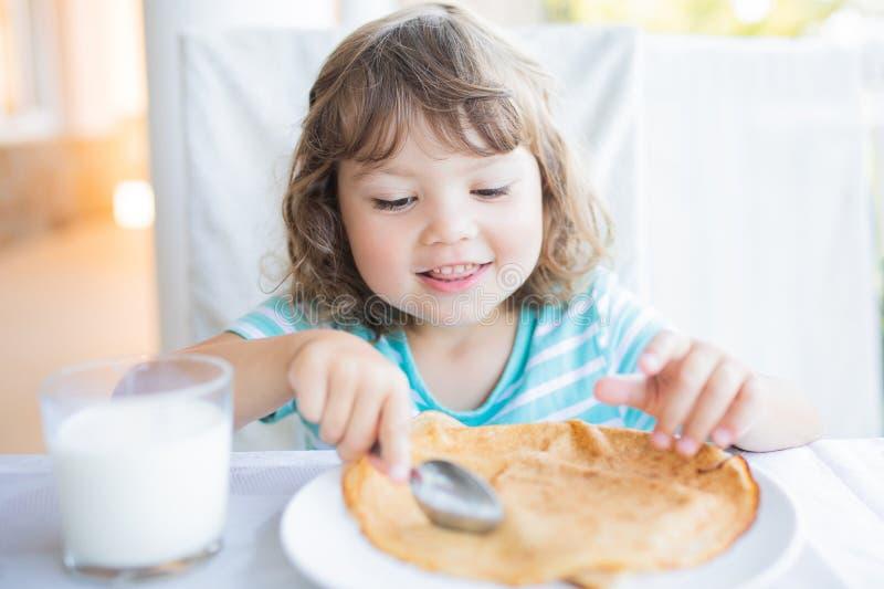 Menina adorável que come o café da manhã, comendo panquecas e o leite bebendo imagem de stock