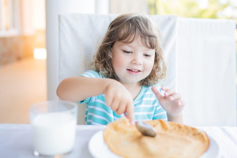 Menina adorável que come o café da manhã, comendo panquecas e o leite bebendo foto de stock royalty free