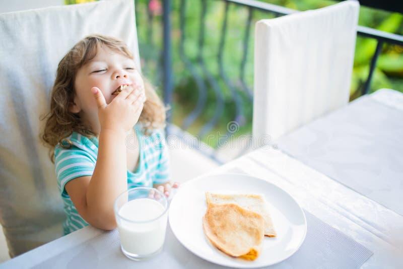 Menina adorável que come o café da manhã, comendo panquecas e o leite bebendo fotografia de stock