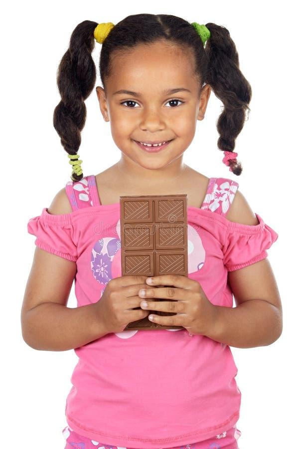 Menina adorável que come o chocolate fotografia de stock