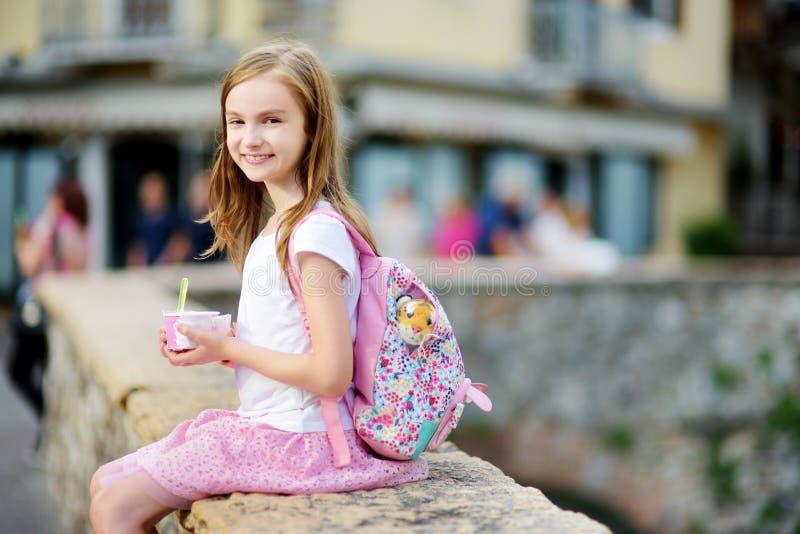 Menina adorável que come o gelado fresco saboroso fora no dia de verão morno imagens de stock royalty free
