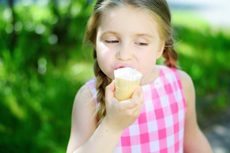 Menina adorável que come o gelado saboroso no dia de verão imagem de stock