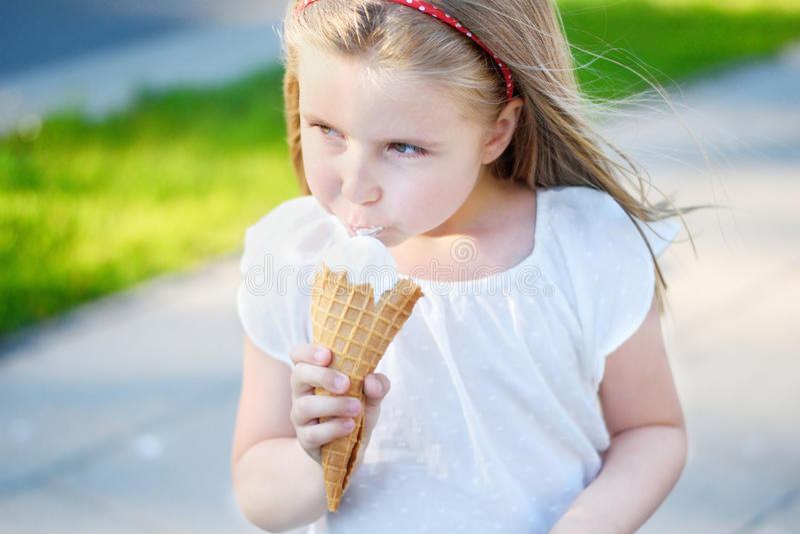 Menina adorável que come o gelado saboroso no parque no dia de verão ensolarado morno imagens de stock royalty free