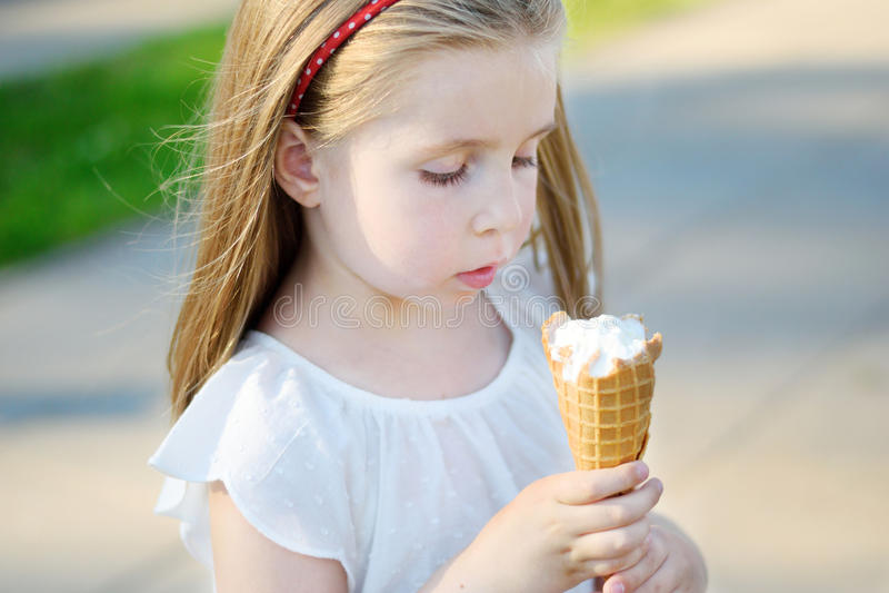 Menina adorável que come o gelado saboroso no parque no dia de verão ensolarado morno fotografia de stock