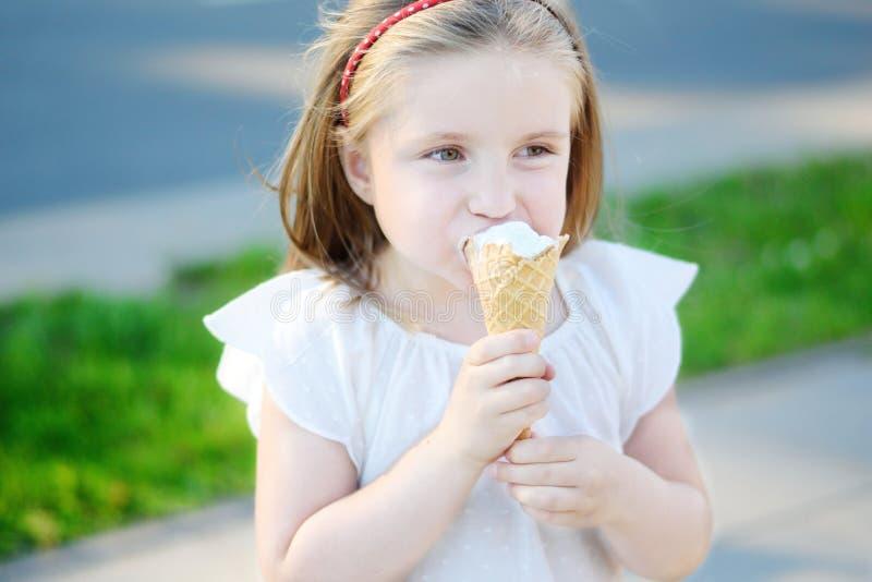 Menina adorável que come o gelado saboroso no parque no dia de verão ensolarado morno fotos de stock royalty free