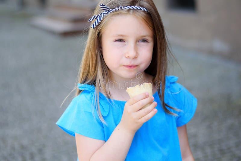 Menina adorável que come o gelado saboroso no parque no dia de verão ensolarado morno fotografia de stock royalty free