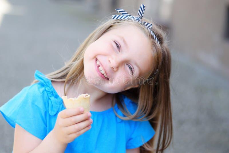 Menina adorável que come o gelado saboroso no parque no dia de verão ensolarado morno imagem de stock