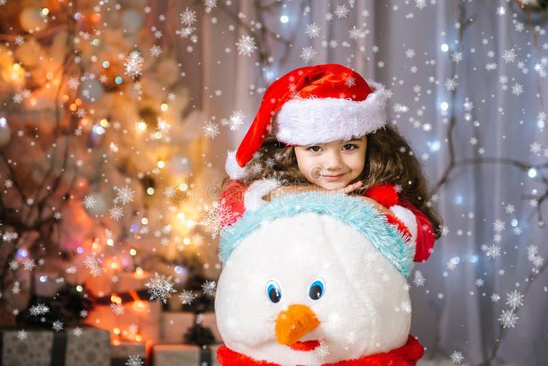 Menina adorável que constrói um boneco de neve no parque bonito do inverno Criança bonito que joga em uma neve Atividades do inve foto de stock royalty free