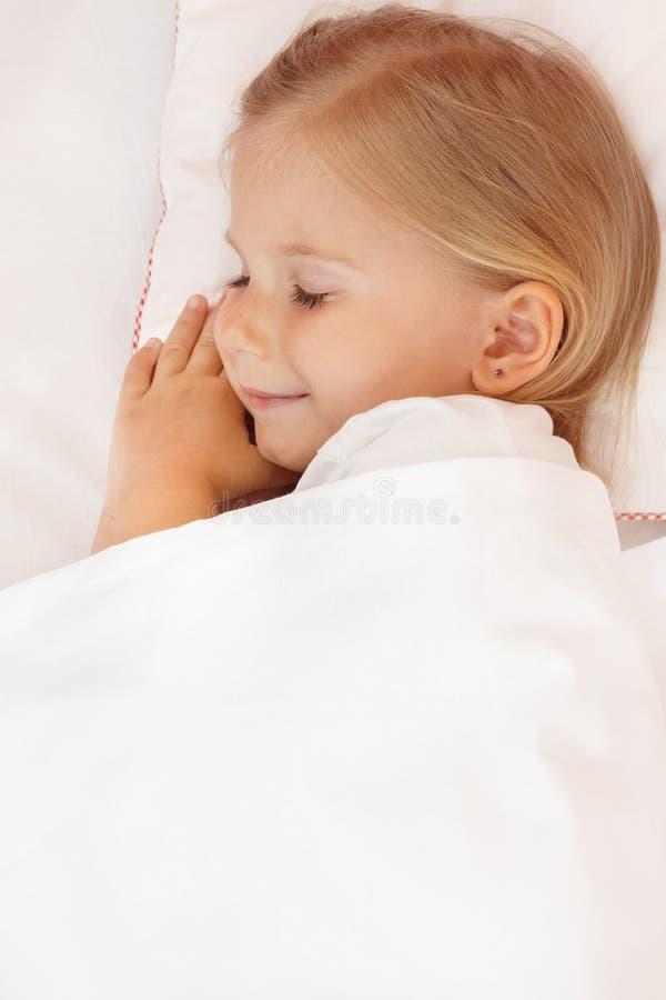Menina adorável que dorme na cama foto de stock