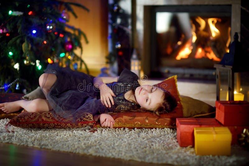 Menina adorável que dorme sob a árvore de Natal por uma chaminé na Noite de Natal foto de stock royalty free