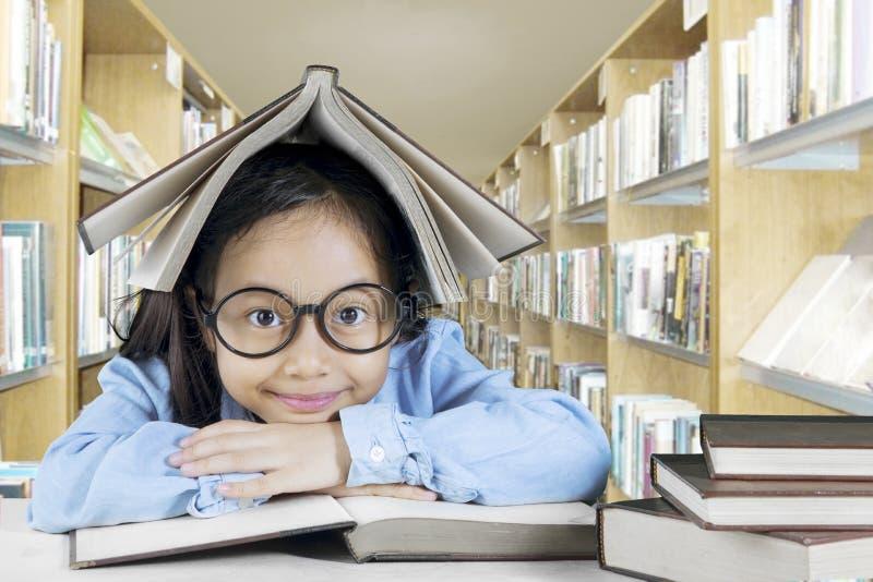 Menina adorável que estuda na biblioteca imagens de stock