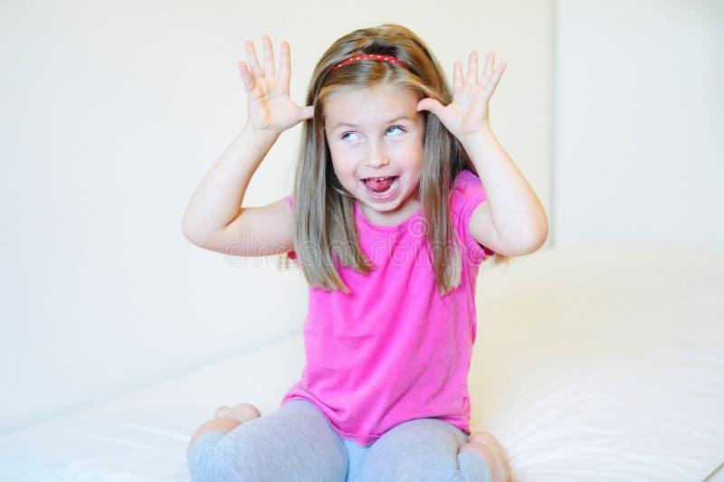 Menina adorável que faz as caras engraçadas fotografia de stock