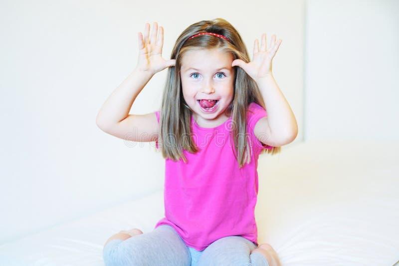 Menina adorável que faz as caras engraçadas fotos de stock