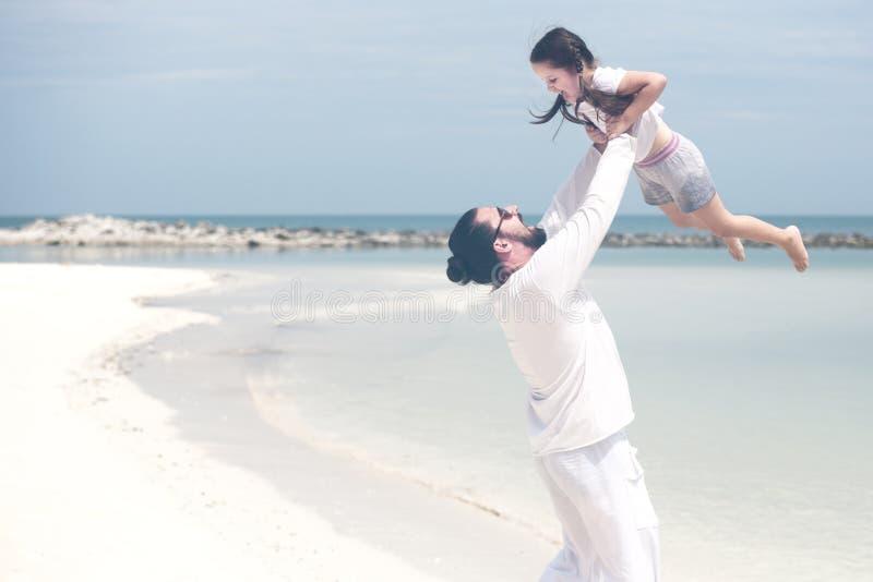 Menina adorável que guarda sua mão do pai Pai e filha que jogam junto na praia imagem de stock
