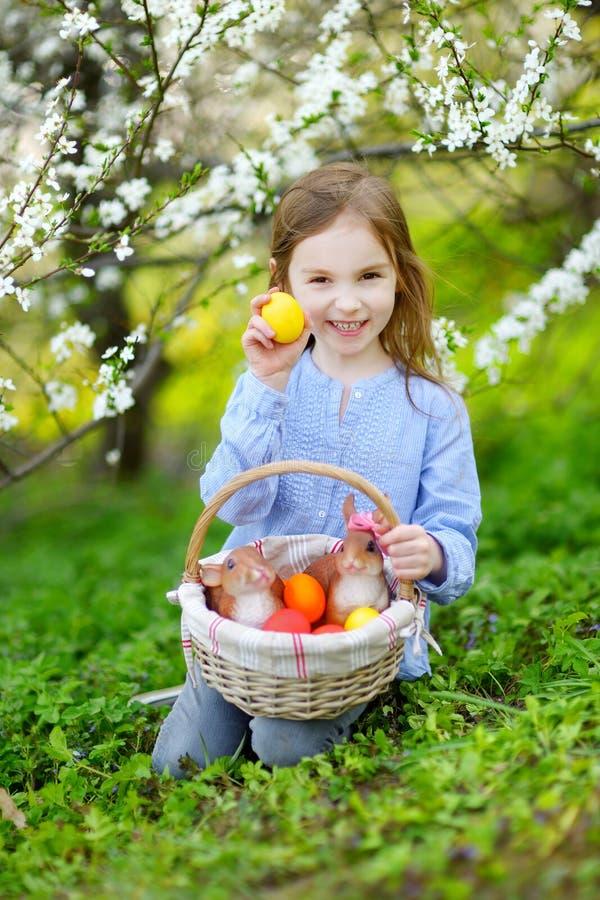 Menina adorável que guarda uma cesta dos ovos da páscoa fotografia de stock royalty free