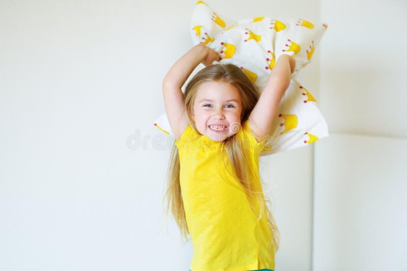 Menina adorável que joga com o descanso na cama em seu quarto imagens de stock