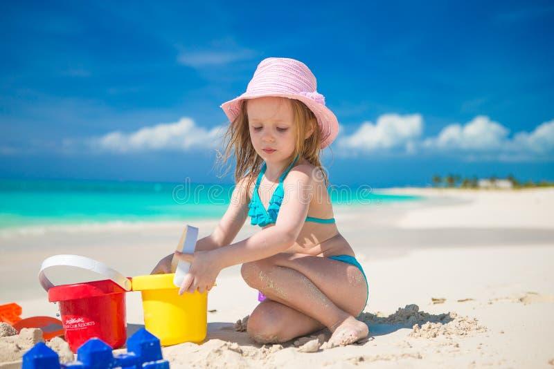 Menina adorável que joga com os brinquedos na praia imagens de stock